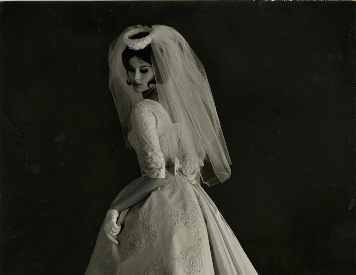 "NMAH Archives Center Priscilla of Boston Collection 0557 Box 5 Folder 1 Publicity photo of model in wedding dress ""565 The Fan Pleated Silhouette"", 1962"