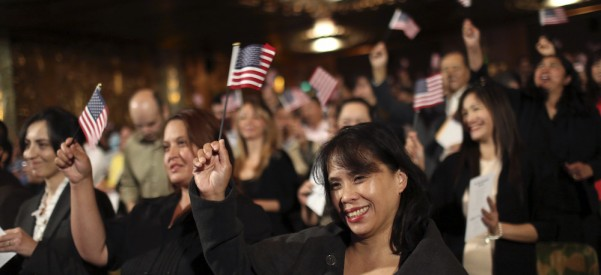Immigrants wave flags following a U.S. Citizenship and Immigration Services ceremony in Oakland, California August 13, 2014. About 1,000 immigrants from 97 countries attended the ceremony. REUTERS/Robert Galbraith  (UNITED STATES - Tags: POLITICS SOCIETY IMMIGRATION) - RTR42BW2