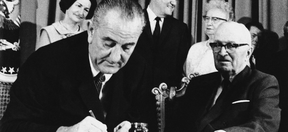 President Lyndon Johnson signs the Medicare Bill into law while former President Harry S. Truman, right, observes during a ceremony at the Truman Library in Independence, Mo. on July 30, 1965. Photo courtesy of Associated Press.