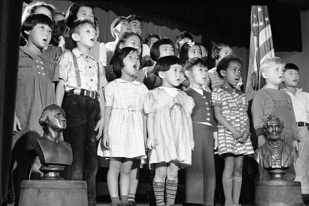 "Flanked by the busts of George Washington and Abraham Lincoln, students at Seattle's Bailey-Gatzert School sing ""America"" on November 24, 1941. Photo courtesy of Associated Press."