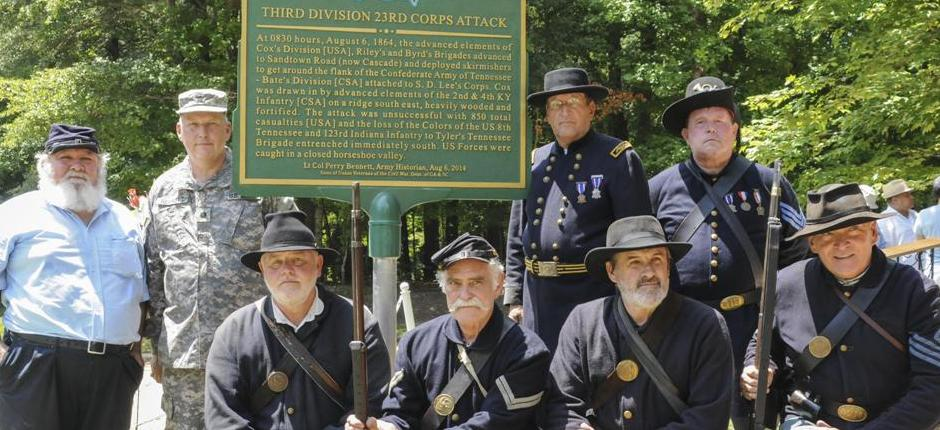 Civil War re-enactors pose in their Union battle regalia at a historic marker. Photo courtesy of Sgt. Stephanie Hargett/U.S. Army Reserve.