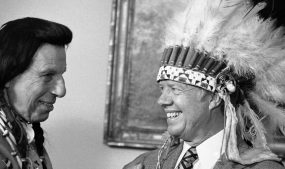 """Iron Eyes Cody presents President Jimmy Carter with a Native American headdress in the Oval Office in Washington on April 21, 1978. Cody also gave Carter a Native American name, Wamblee Ska, which he said means """"great white eagle."""" Photo courtesy of Peter Bregg/Associated Press."""