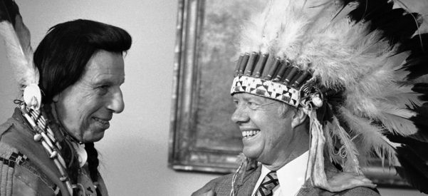 "Iron Eyes Cody presents President Jimmy Carter with a Native American headdress in the Oval Office in Washington on April 21, 1978. Cody also gave Carter a Native American name, Wamblee Ska, which he said means ""great white eagle."" Photo courtesy of Peter Bregg/Associated Press."