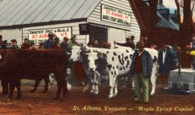 """Postcard depicting St. Albans, Vermont, """"Maple Syrup Capital of U.S.,"""" circa 1930-1945. Image courtesy of Wikimedia Commons."""